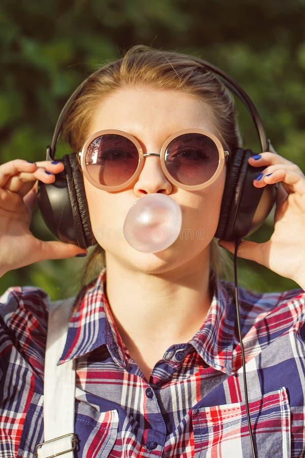 Hipstermeisje het luisteren aan muziek op hoofdtelefoons en kauwt de herkauwmassa stock afbeelding
