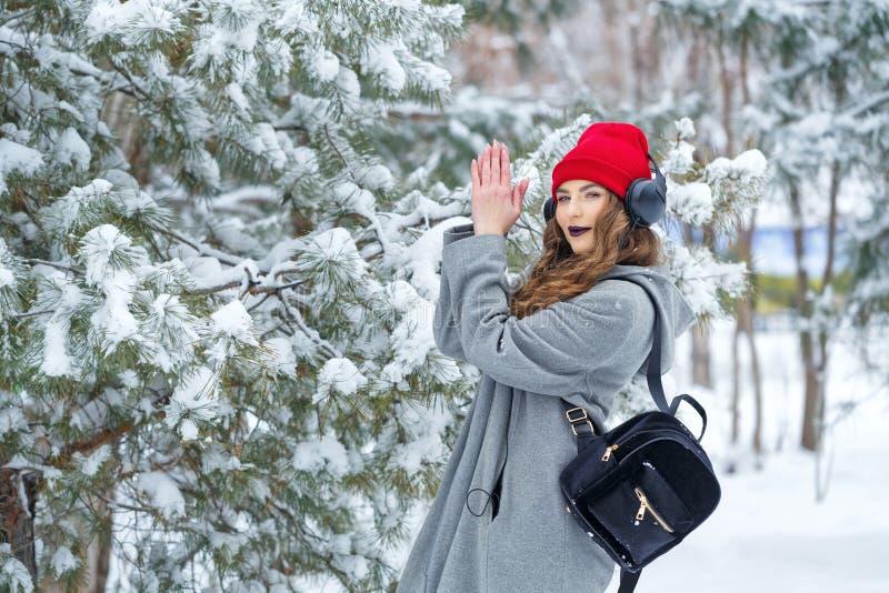 Hipstermeisje het luisteren muziek in de winter stock afbeelding