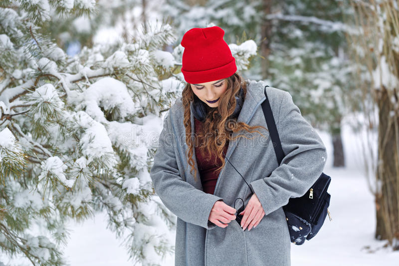 Hipstermeisje het luisteren muziek in de winter stock fotografie