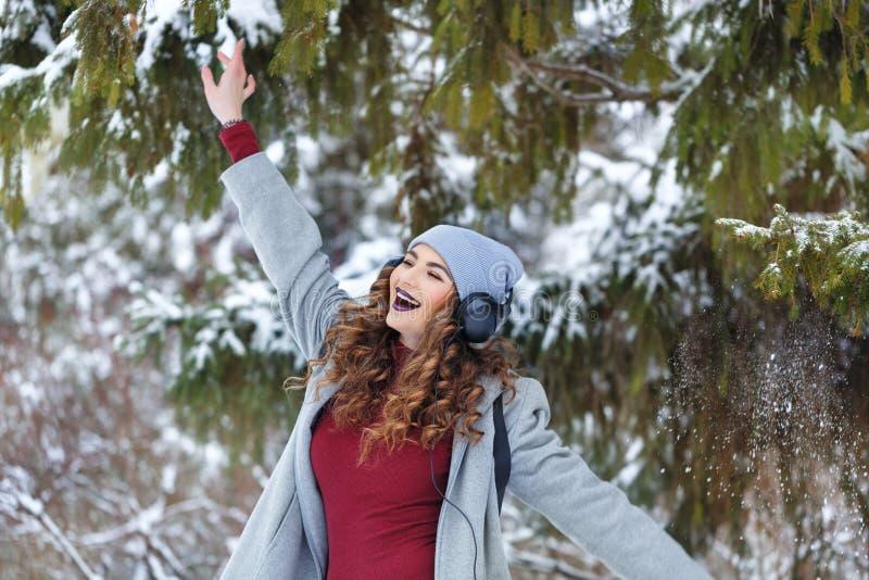 Hipstermeisje het luisteren muziek en het dansen in de winter stock foto's