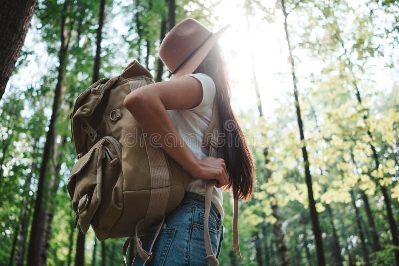 Hipstermeisje het reizen alleen en het kijken rond in bos bij in openlucht het dragen van treveler rugzak en greepplaats brengen  royalty-vrije stock foto