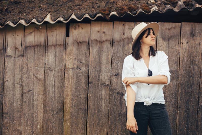 Hipstermeisje in het witte toevallige uitrusting stellen op achtergrond van oude houten cabine in bergen Modieuze vrouw in hoed d royalty-vrije stock foto