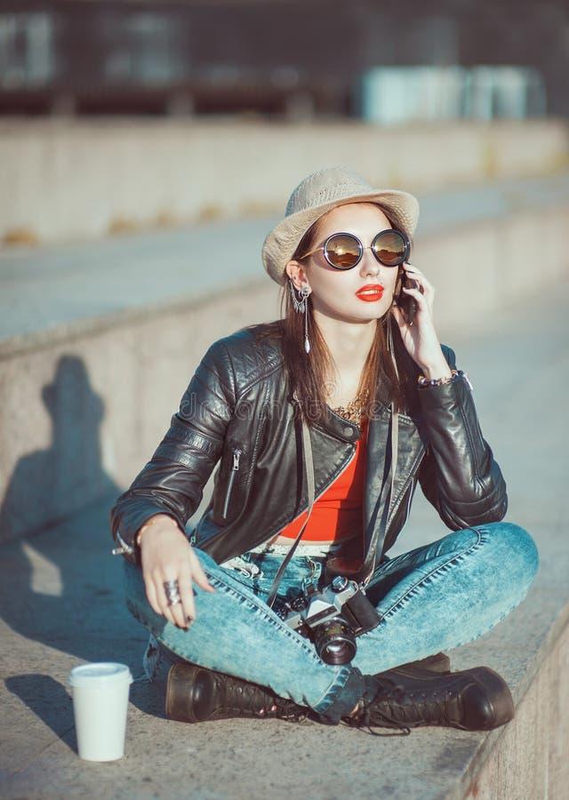Hipstermeisje in leerjasje, hoed met retro camera en mobiel royalty-vrije stock fotografie