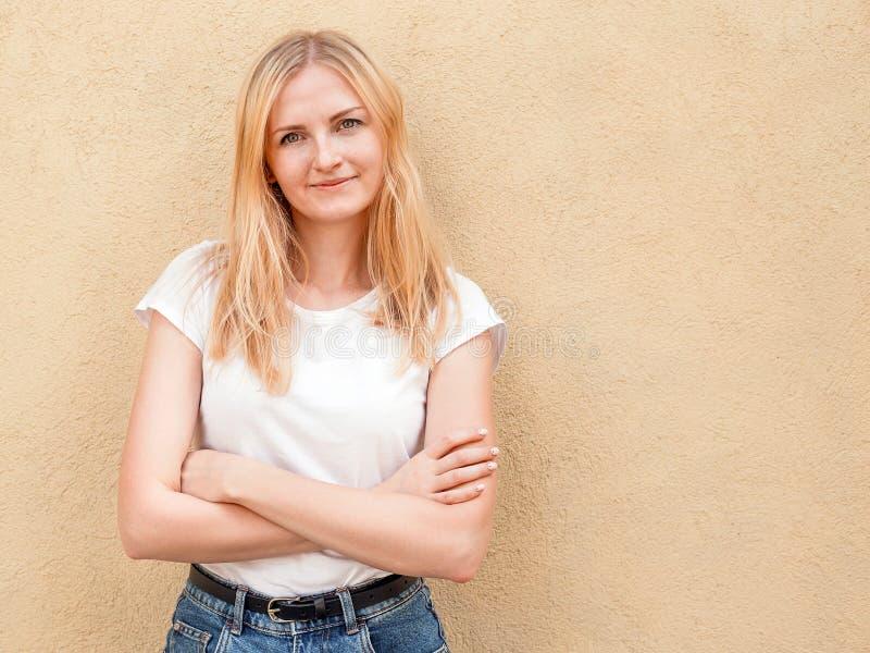 Hipstermeisje lege witte t-shirt dragen en jeans die tegen ruwe straatmuur stellen, minimalistische stedelijke kledingsstijl stock afbeeldingen