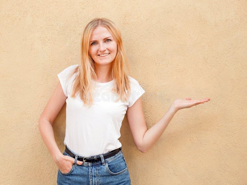 Hipstermeisje lege witte t-shirt dragen en jeans die tegen ruwe straatmuur stellen, minimalistische stedelijke kledingsstijl royalty-vrije stock foto