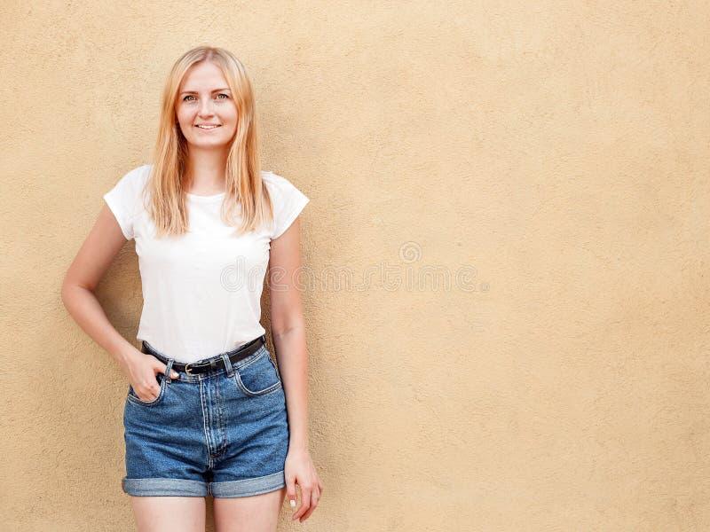 Hipstermeisje lege witte t-shirt dragen en jeans die tegen ruwe straatmuur stellen, minimalistische stedelijke kledingsstijl royalty-vrije stock afbeeldingen