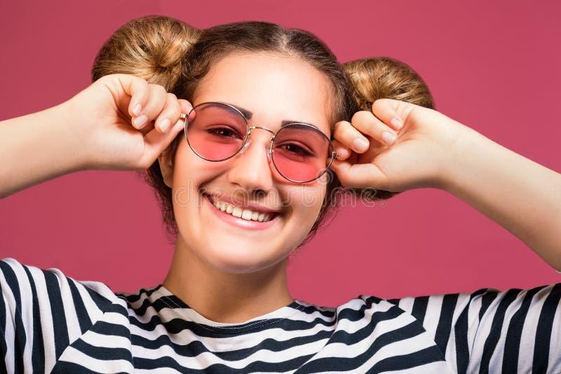Hipstermeisje in zonnebril en gestreept overhemd met speels die kapsel over roze achtergrond wordt geïsoleerd royalty-vrije stock foto's