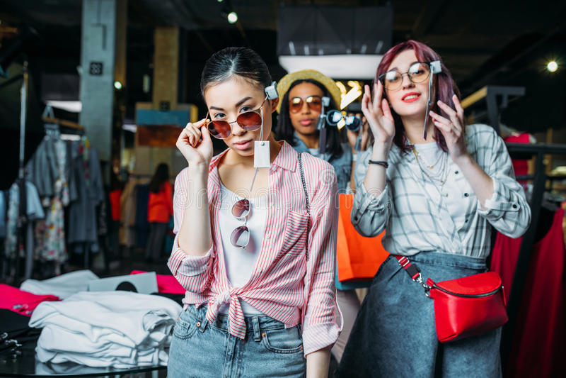 Hipstermeisjes die kleren in boutique, manier het winkelen meisjesconcept kiezen stock foto