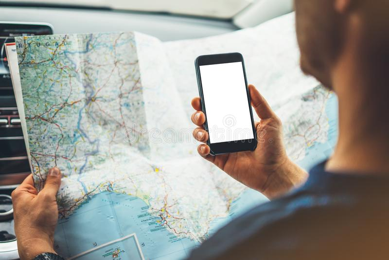 Hipstermens die op navigatiekaart kijken in auto, toeristenreiziger die en in mannelijke gps van handensmartphone met het schone  royalty-vrije stock foto