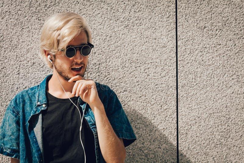 Hipstermens het luisteren muziek door oortelefoons stock afbeeldingen