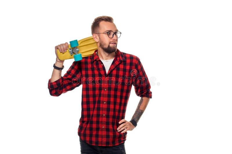 Hipstermens over witte achtergrond die geel skateboard houden Actieve kerel in plaidoverhemd met exemplaarruimte royalty-vrije stock afbeeldingen