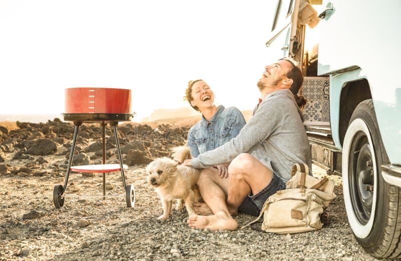 Hipsterpaar met leuke hond die samen op minivan oldtimer reizen royalty-vrije stock afbeelding