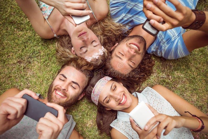 Hipsters som ligger på gräs genom att använda smartphones fotografering för bildbyråer