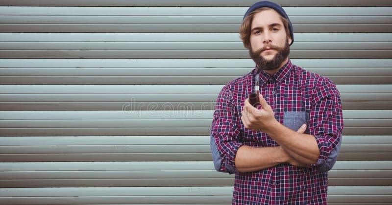 Hipsters som rymmer att röka röret mot väggen arkivfoton