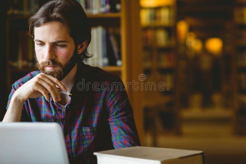 Hipsterstudent die in bibliotheek bestuderen stock afbeeldingen