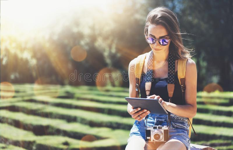 Hipsterung flicka med den ljusa ryggs?ck- och tappningkameran genom att anv?nda minnestavlan eller rymma grejen som planerar lopp arkivbild