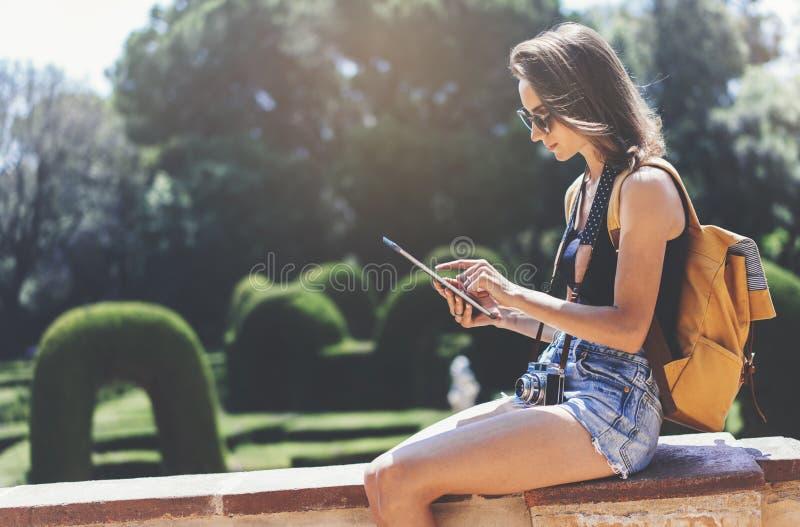 Hipsterung flicka med den ljusa ryggs?ck- och tappningkameran genom att anv?nda minnestavlan eller rymma grejen som planerar lopp royaltyfri bild