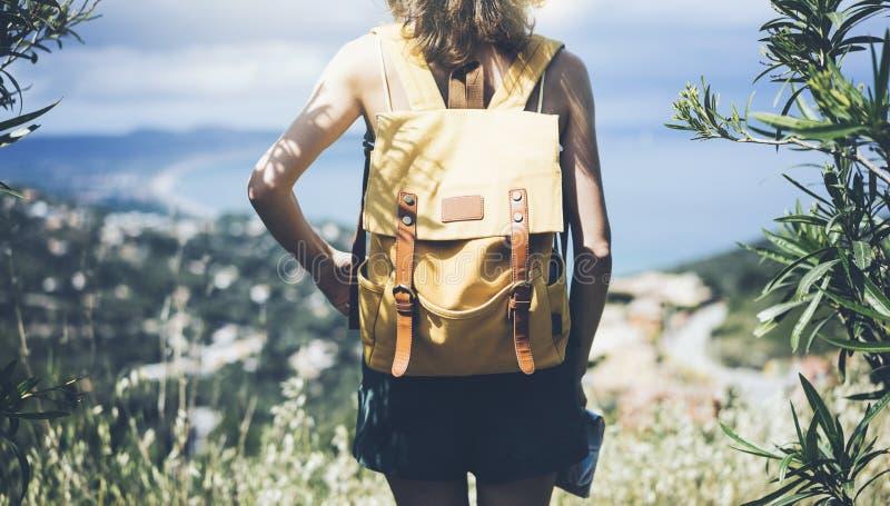 En ung flicka med lysande ryggsäck som tittar på en karta och pekar hand på reseplanen Visa från turistrets baksida royaltyfri fotografi