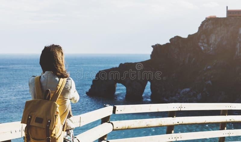 Hipsterung flicka med ryggsäcken som tycker om solnedgång på seascape på det maximala berget Turist- handelsresande på bakgrundsd royaltyfri bild