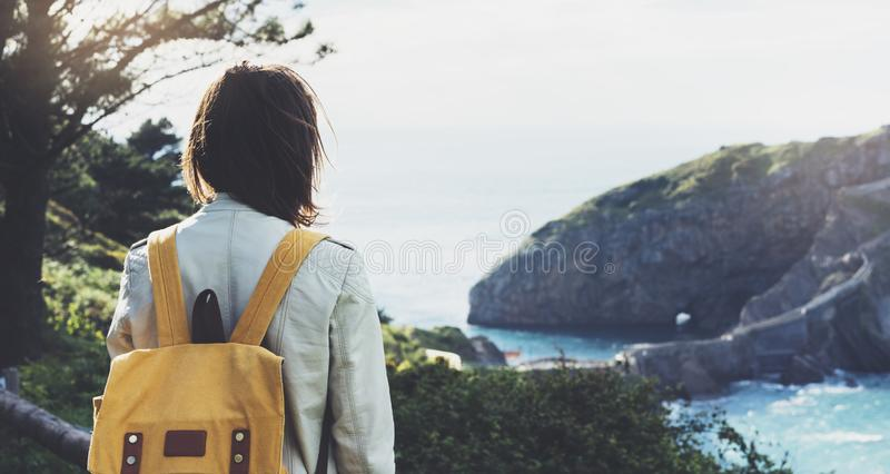 Hipsterung flicka med ryggsäcken som tycker om solnedgång på seascape på det maximala berget Turist- handelsresande på bakgrundsd fotografering för bildbyråer
