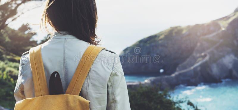Hipsterung flicka med ryggsäcken som tycker om solnedgång på seascape på det maximala berget Turist- handelsresande på bakgrundsd royaltyfri foto