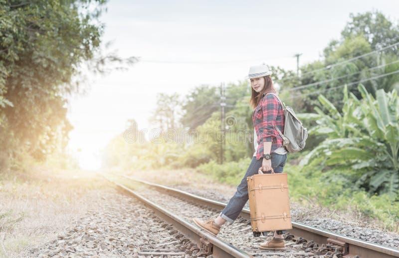 Hipsterunga flickan med ryggsäcken går på järnväg arkivfoto
