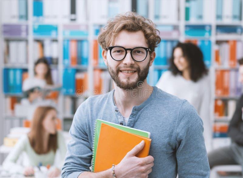 Hipsteruniversitetsstudent som rymmer anteckningsböcker arkivbilder