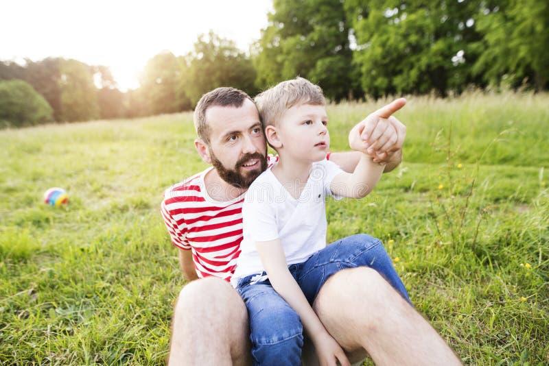 Hipstervader en weinig zoon op groene weide Zonnige de zomerdag royalty-vrije stock foto