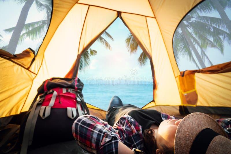 Hipstervrouw die en in de tentpicknick op vakantie met de mooie overzeese meningsachtergrond rusten slapen stock foto