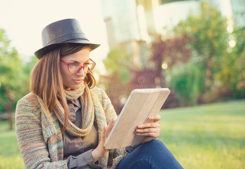 Hipstervrouw die tablet in park gebruiken royalty-vrije stock foto's