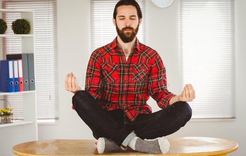 Hipsterzakenman die bij zijn bureau mediteren stock foto