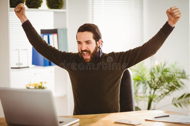 Hipsterzakenman die bij zijn bureau toejuichen stock fotografie