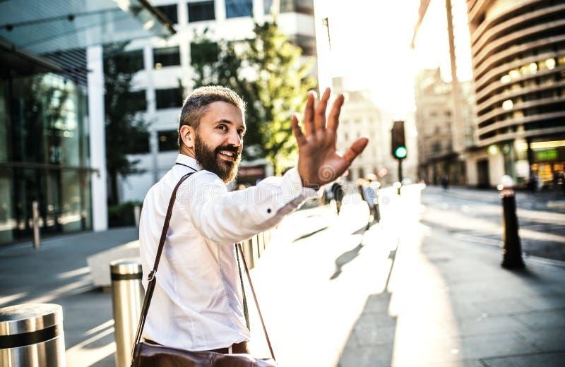 Hipsterzakenman die omhoog de straat in Londen lopen, terug en somebody begroeten kijken royalty-vrije stock foto's