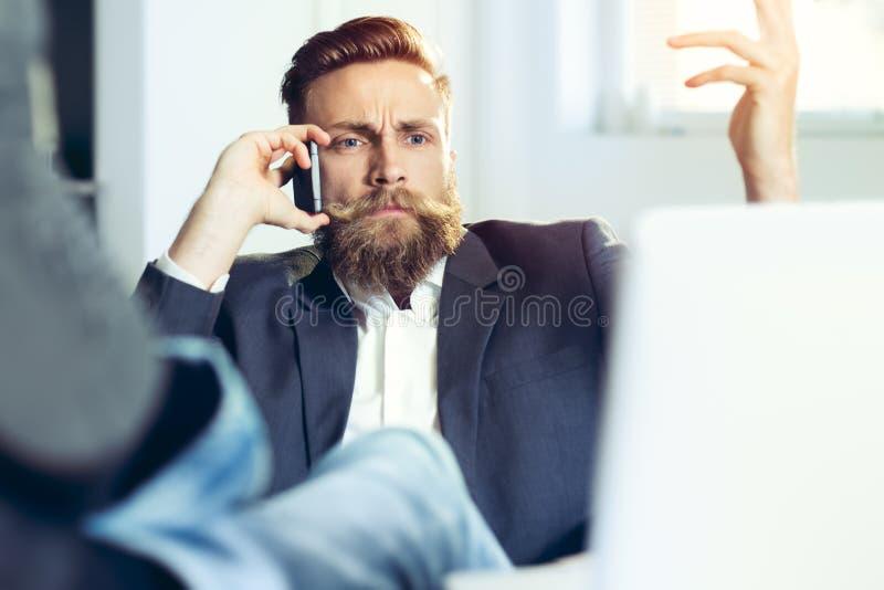 Hipsterzakenman het ontspannen bij zijn bureau in zijn bureau royalty-vrije stock afbeelding