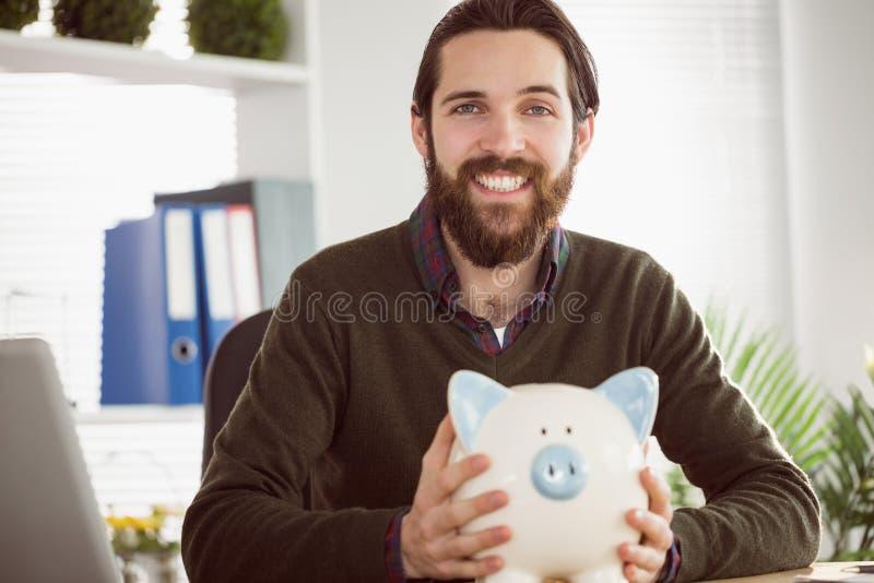 Hipsterzakenman met een spaarvarken stock foto