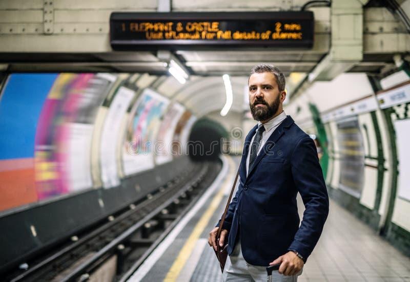 Hipsterzakenman met een zak die op de trein in metro wachten royalty-vrije stock afbeelding