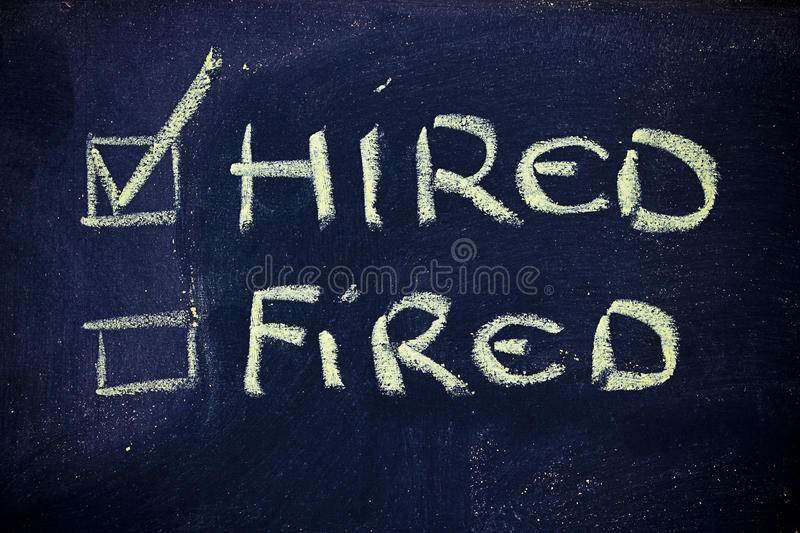Hired vs.fired. Chalk writings on blackboard, hired vs. fired royalty free stock photo