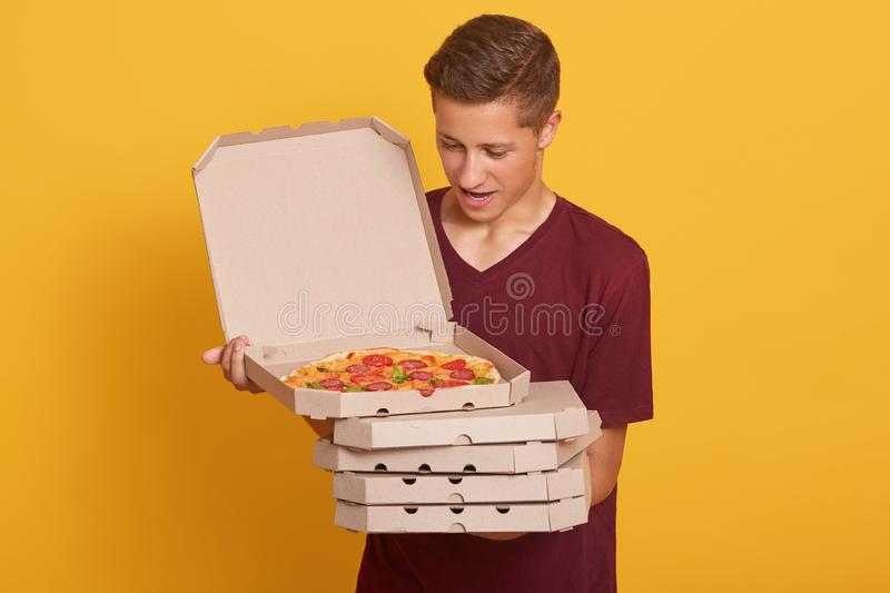 Hirizontal shot of handsome man wearing burgundy casual t shirt, holding stack of pizza boxes in hands, looking at opened box, stock photo