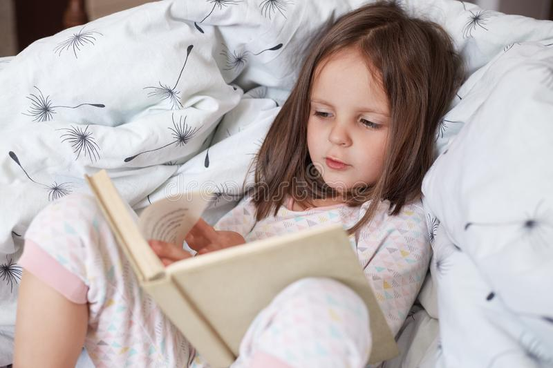 Hirizontal shot of happy girl lying in bed on blanket, reading interesting book,has concentrated facial expression, female child stock image