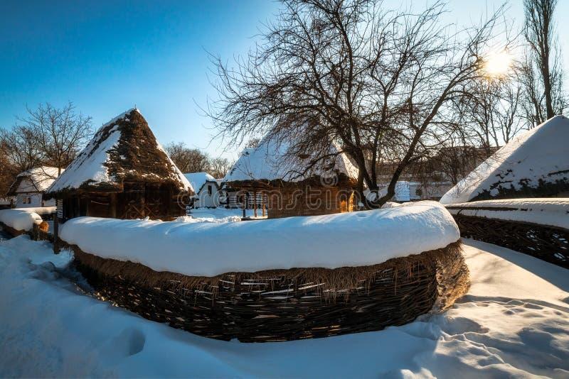 Hirtenlandschaft mit traditionellen alten Häuschen mit einem Strohdach bedeckt im Schnee lizenzfreies stockbild