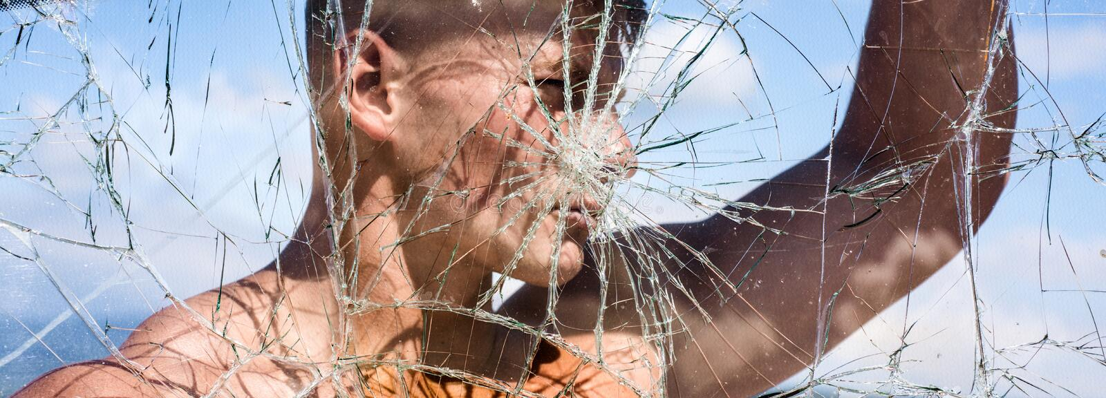His ambition knows no bounds. Strong man seen through cracked glass. Sport man with muscular strength. Sport club. Achieving sport ambition with right workout stock images