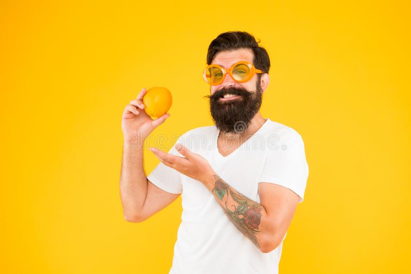 His diet plan. Bearded man pointing at orange on yellow background. Hipster choosing citrus fruit for detox diet. A stock images