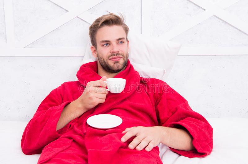 His favorite morning beverage. Handsome guy in bathrobe holding cup of hot drink. Bearded caucasian man enjoying his stock image
