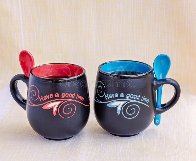 His and Her Mugs of Tea. Black ceramic mugs of steaming tea with spoons and red and blue writing stock photography