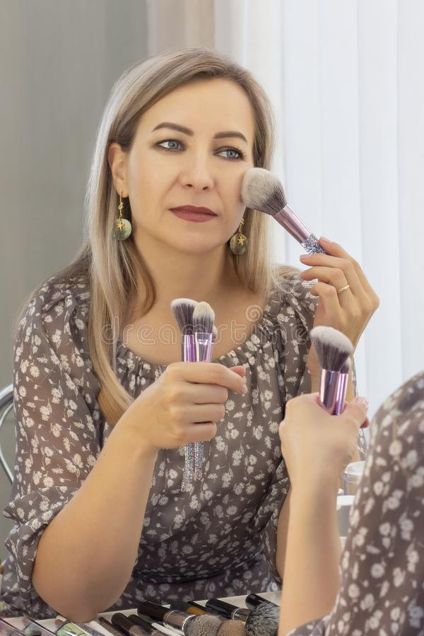His own makeup artist. woman doing makeup in front of a mirror. aged woman stock photography