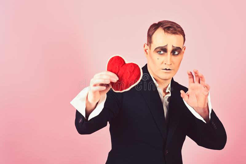 His story of boundless love. Theatre actor pantomime falling in love. Mime actor with love symbol. Mime man hold red stock image