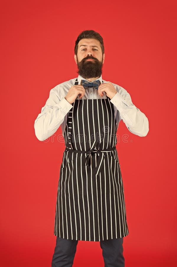 His style works really well to compliment beard. Bearded man fixing bow tie in bib apron. Elegant hipster with bearded. Face. Bearded bartender or cook in work royalty free stock photography