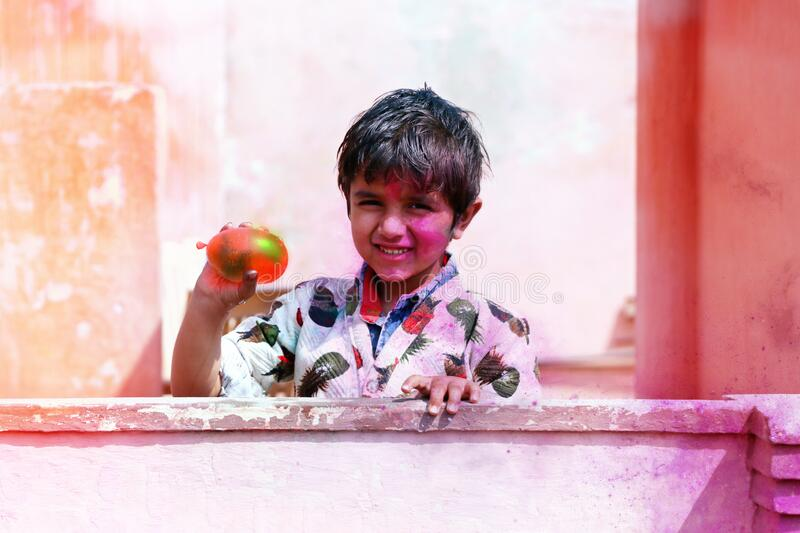 Hisar, haryana, india march 2019, Little boy plays with colors.& balloons Concept for Indian festival. Holi royalty free stock images