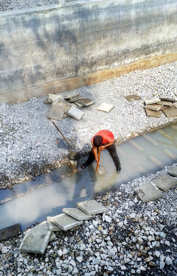 Hisar, Haryana, INDIA - September 2018: indian labours mixing building material. On construction site royalty free stock image