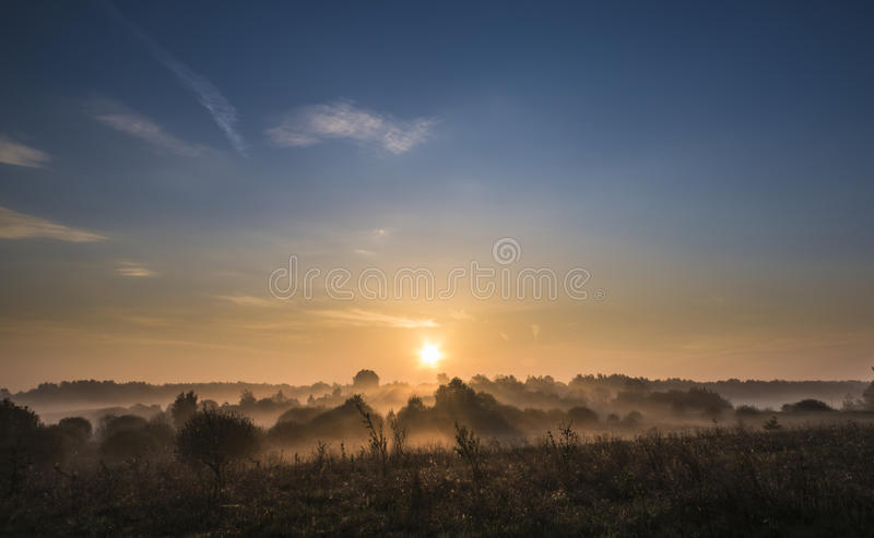 Hisnande dimmigt landskap med resningsolen över fältet arkivfoton